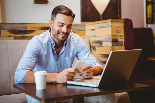 Homme d'affaires souriant envoyant un message texte