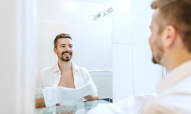 Homme d'affaires souriant et gai avec une chemise déboutonnée et une serviette dans ses mains se lavant le visage en se tenant debout devant le miroir dans la salle de bain.