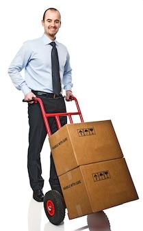 Homme d'affaires souriant avec handtruck rouge et boîtes