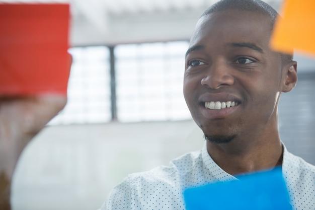 Homme d'affaires souriant, lecture de notes autocollantes sur verre