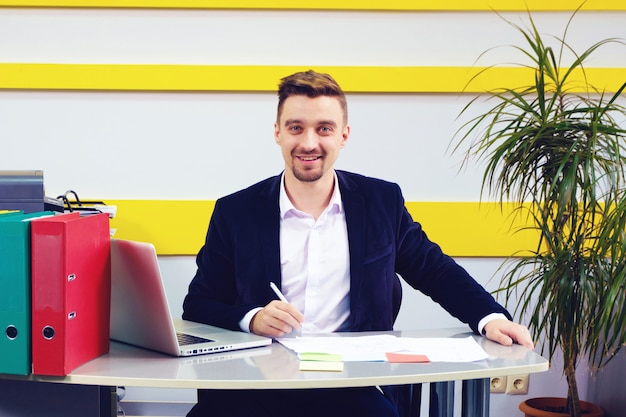 Un homme d'affaires souriant sur le lieu de travail