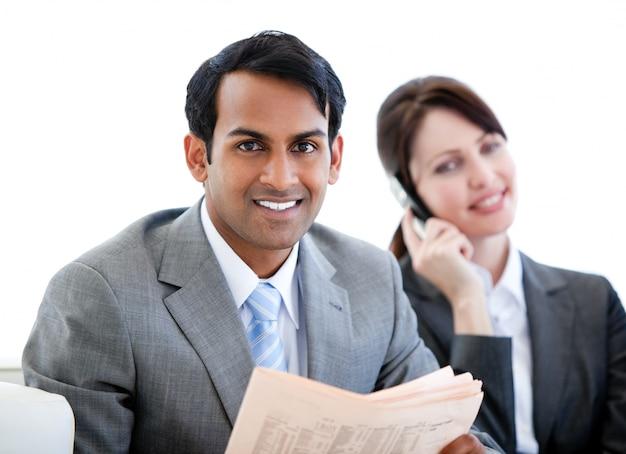 Homme d'affaires souriant, lisant un journal dans une salle d'attente