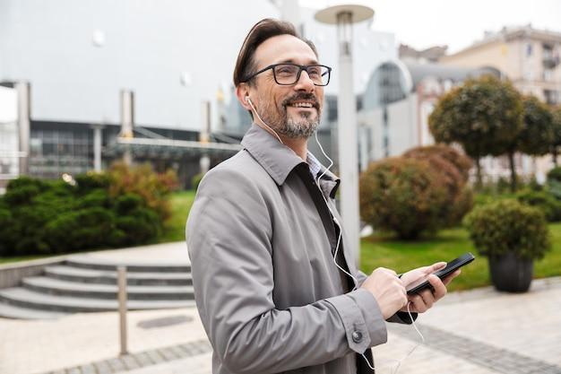 Homme d'affaires souriant à lunettes utilisant un téléphone portable et des écouteurs en marchant dans la rue de la ville