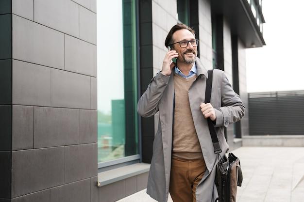 Homme d'affaires souriant mature à lunettes parlant au téléphone portable tout en marchant près d'un immeuble de bureaux en zone urbaine