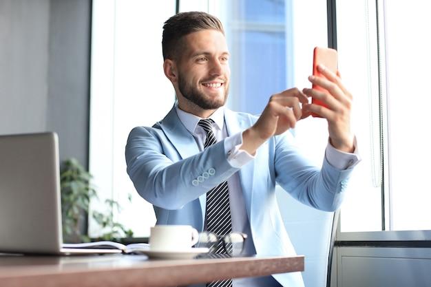 Un homme d'affaires souriant moderne fait du selfie au bureau.