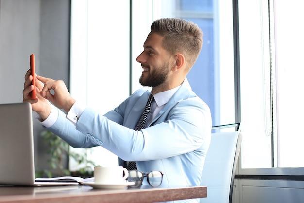 Un homme d'affaires souriant moderne prend un selfie au bureau.