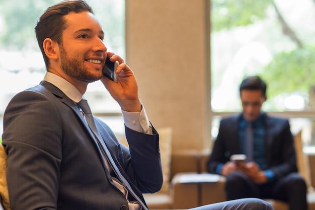 Homme d'affaires souriant parlant au téléphone dans le salon