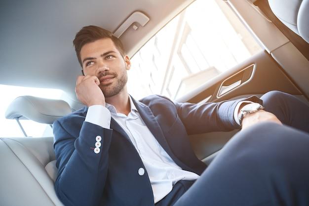 Homme d'affaires souriant parlant au téléphone intelligent et assis sur la banquette arrière de la voiture