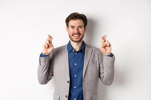 Homme d'affaires souriant plein d'espoir à la recherche optimiste, croiser les doigts bonne chance