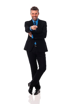Homme d'affaires souriant, pointant vers le côté de la caméra