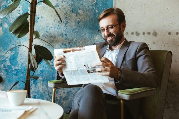 Homme d'affaires souriant portant costume lisant le journal alors qu'il était assis au café et buvant du café