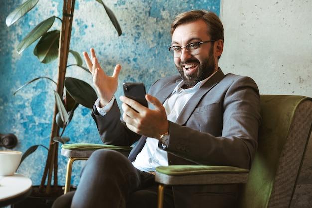 Homme d'affaires souriant portant costume tenant un téléphone portable alors qu'il était assis au café et buvant du café