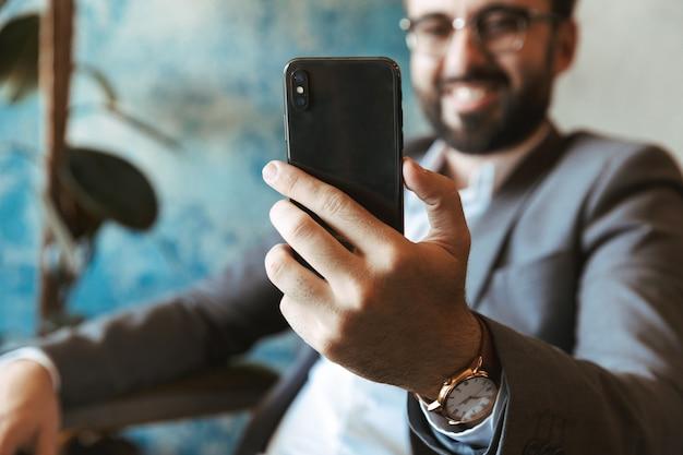 Homme d'affaires souriant portant costume tenant un téléphone portable alors qu'il était assis au café