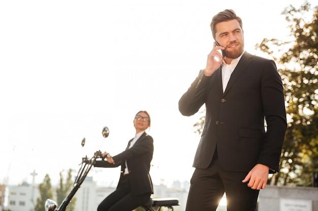 Homme d'affaires souriant posant à l'extérieur parler par téléphone