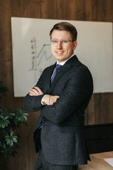 Un homme d'affaires souriant prospère est debout dans un costume classique au bureau.