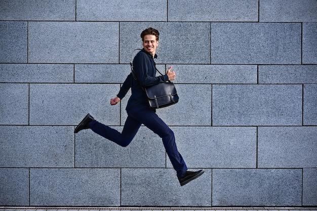 Homme d'affaires souriant qui court vite avec une mallette en ville