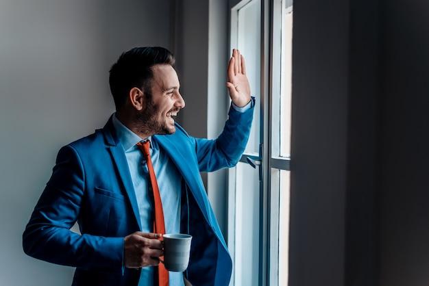 Homme d'affaires souriant, saluant un ami par la fenêtre.