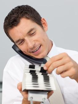 Homme d'affaires souriant sur le téléphone et consultant un titulaire de la carte