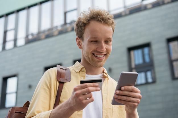 Homme d'affaires souriant tenant une carte de crédit à l'aide d'un smartphone pour faire des achats en ligne, debout dans la rue
