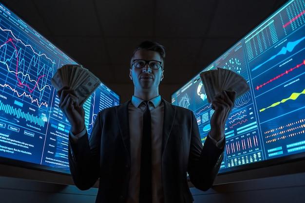 L'homme d'affaires souriant tenant des dollars dans ses mains