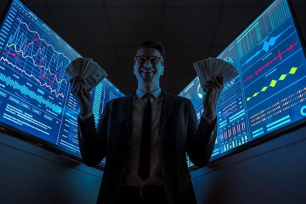 L'homme d'affaires souriant tenant la monnaie dans ses mains