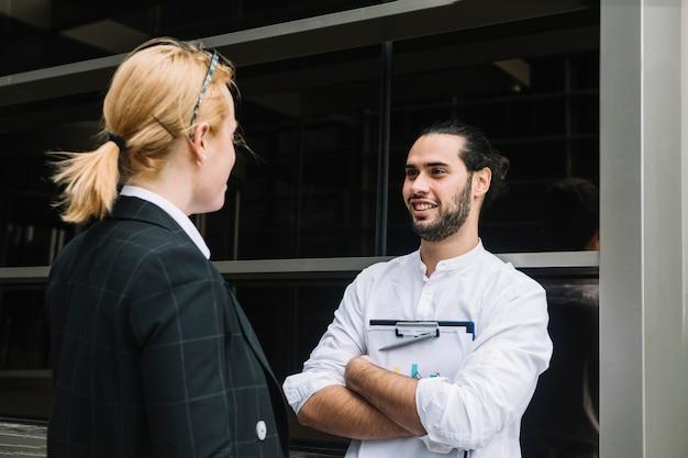 Homme d'affaires souriant tenant le presse-papiers parlant à une femme d'affaires