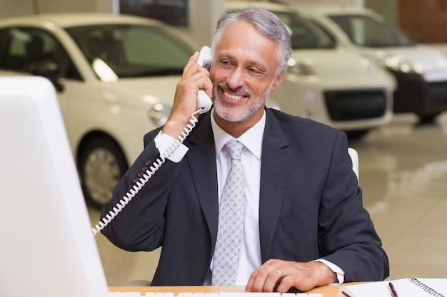 Homme d'affaires souriant en utilisant le téléphone en face de l'ordinateur