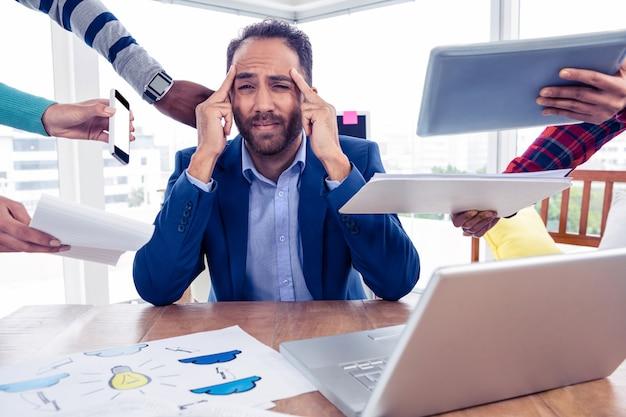 Homme d'affaires stressant assis par des collègues de bureau créatif
