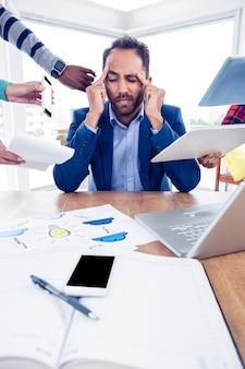 Homme d'affaires stressant assis avec la tête dans les mains au bureau de création