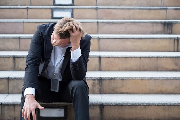 Homme d'affaires stressé assis sur les marches