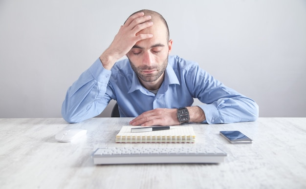 Homme d'affaires stressé caucasien assis et touchant la tête au bureau.