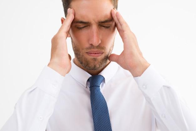 Homme d'affaires stressé touchant les temples et réfléchissant