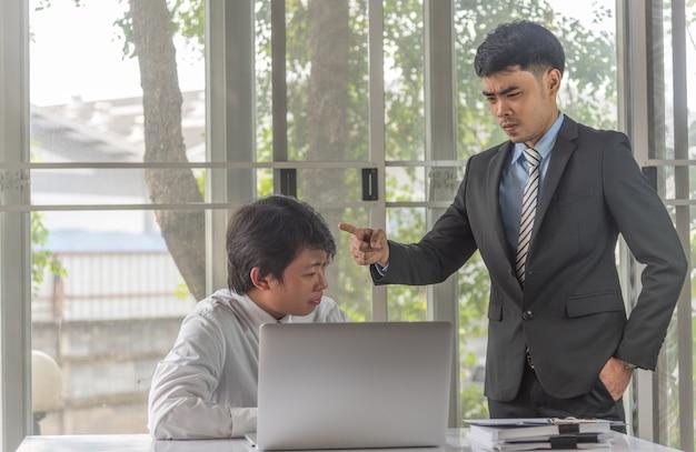 Homme d'affaires stressé travaillant avec ordinateur portable sur le bureau et le patron de l'homme en colère se plaignant debout