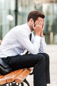 Homme d'affaires stressé. vue latérale d'un jeune homme d'affaires frustré couvrant son visage avec les mains alors qu'il était assis sur le banc à l'extérieur