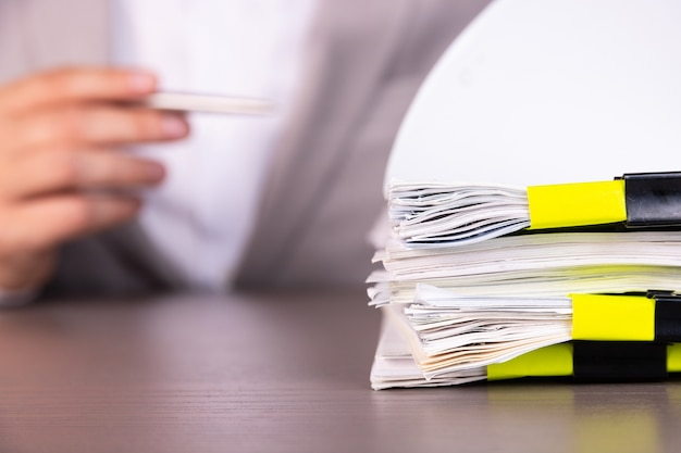 Un homme d'affaires avec un stylo à l'arrière-plan d'une pile de documents maintenus ensemble par des pinces