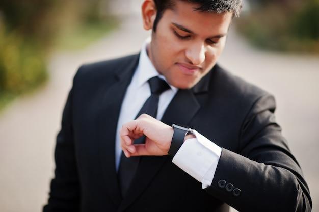 Homme d'affaires sud-asiatique élégant en costume en regardant ses montres intelligentes à portée de main.
