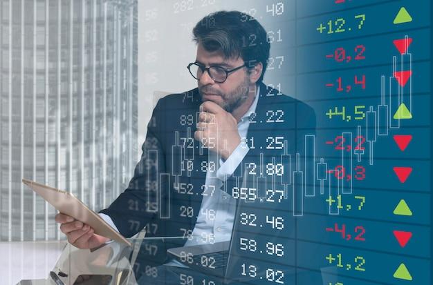 Homme d'affaires suivant l'évolution des graphiques boursiers sur la mise au point sélective de la tablette