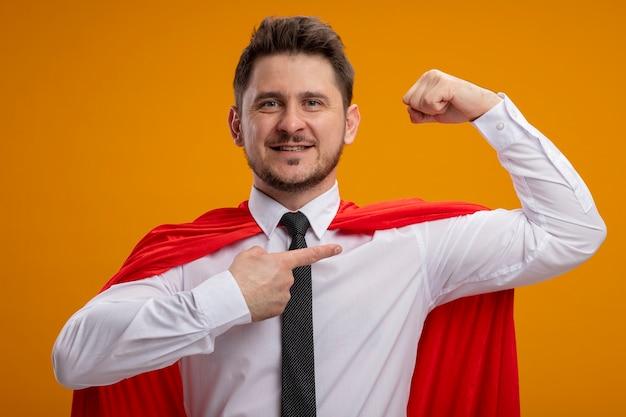 Homme d'affaires de super héros auto-satisfait en cape rouge levant le poing pointant avec l'index au biceps montrant la force à la confiance debout sur le mur orange