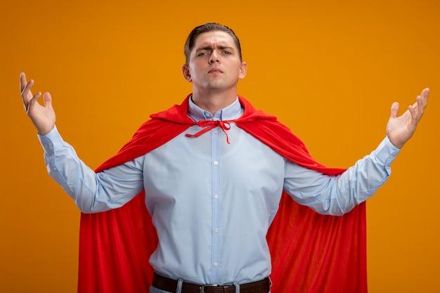 Homme d'affaires de super héros en cape rouge avec les bras levés étant confiant et fier debout sur un mur orange
