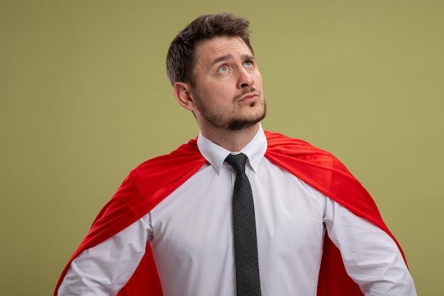 Homme d'affaires de super héros en cape rouge à côté avec une expression confiante sérieuse debout sur le mur vert