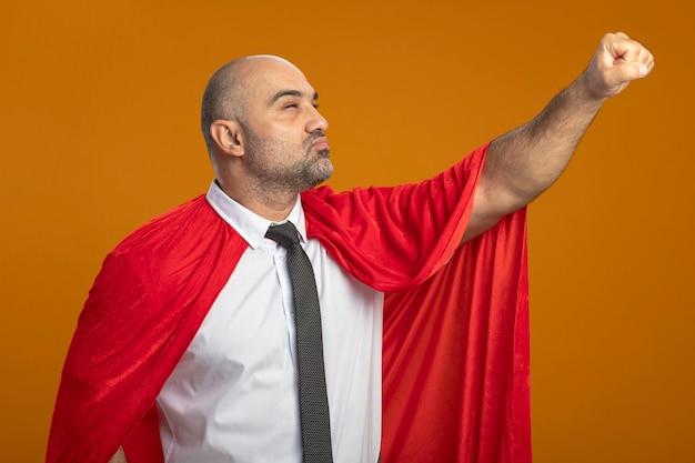 Homme d'affaires de super héros en cape rouge à côté faisant le geste gagnant avec la main prête à aider à la confiance debout sur le mur orange