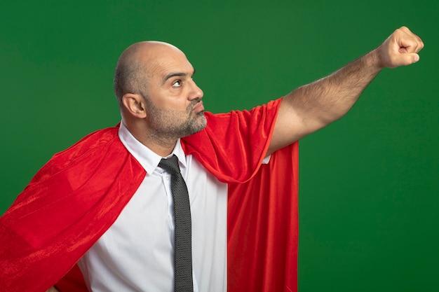 Homme d'affaires de super héros en cape rouge à côté en gardant le bras dans le geste de vol prêt à aider à la confiance debout sur le mur vert