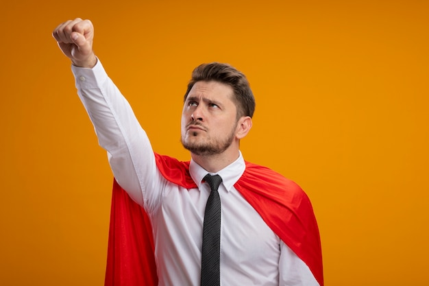 Homme d'affaires de super héros en cape rouge à côté en gardant le bras en geste de vol debout sur un mur orange