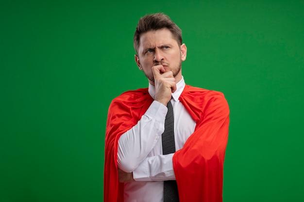 Homme d'affaires de super héros en cape rouge à côté avec la main sur le menton pensant debout sur le mur vert