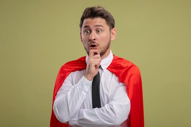 Homme d'affaires de super héros en cape rouge à côté avec la main sur le menton pensant être surpris debout sur fond vert