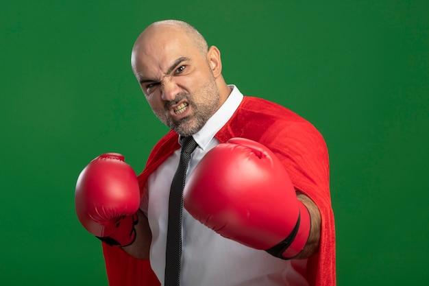 Homme d'affaires de super héros en cape rouge et dans des gants de boxe à l'avant avec un visage en colère prêt à se battre, se présentant comme un boxeur debout sur un mur vert