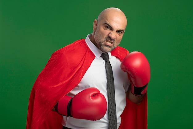Homme d'affaires de super héros en cape rouge et dans des gants de boxe à l'avant avec un visage en colère prêt à se battre se présentant comme un combattant debout sur un mur vert