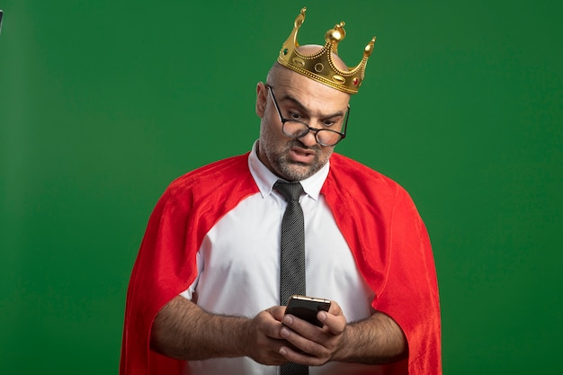 Homme d'affaires de super héros en cape rouge et lunettes portant couronne à l'aide de smartphone à la confusion debout sur le mur vert