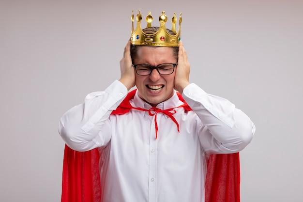 Homme d'affaires de super héros en cape rouge et lunettes portant couronne couvrant les époques avec les mains avec une expression agacée debout sur fond blanc