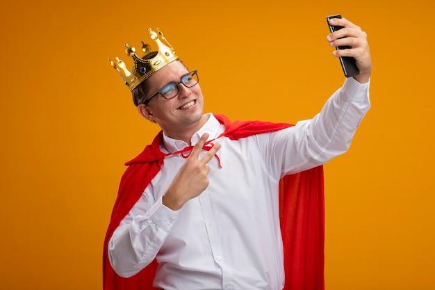 Homme d'affaires de super héros en cape rouge et lunettes portant couronne faisant selfie using smartphone smiling montrant v-sign debout sur un mur orange